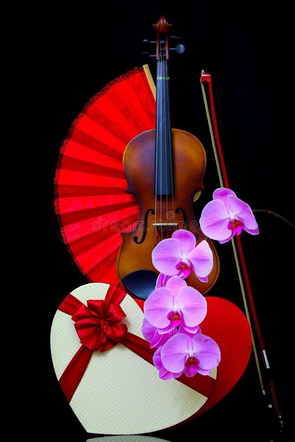深色背景中带蝴蝶结和蝴蝶兰粉色兰花的复古小提琴 免版税图库摄影