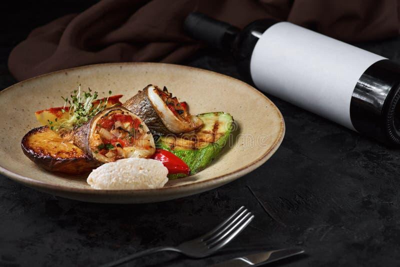深色背景和一瓶葡萄酒盘上的一卷卷多拉多、西葫芦和土豆 库存照片