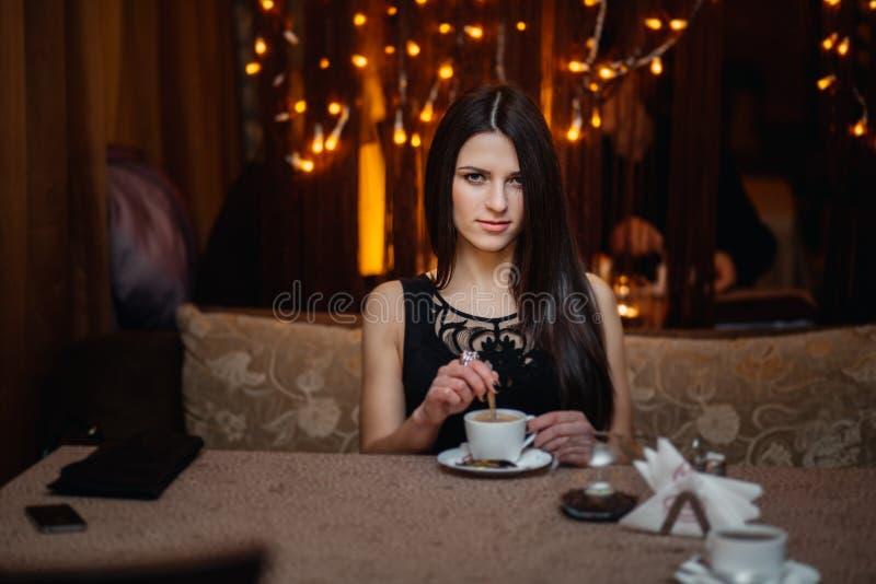 深色头发的坐在一个咖啡馆的妇女长的头发与 免版税库存照片