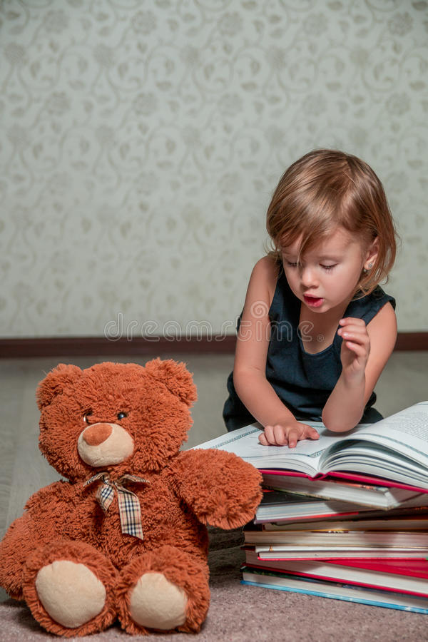 深蓝礼服阅读书的小女孩坐地板在玩具熊附近 孩子读玩具的故事 图库摄影