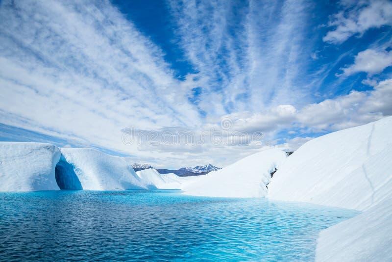 深蓝色冰川水池充斥的冰洞在阿拉斯加 当从融化冰河的水流动了,湖在冰洞填装了 库存图片