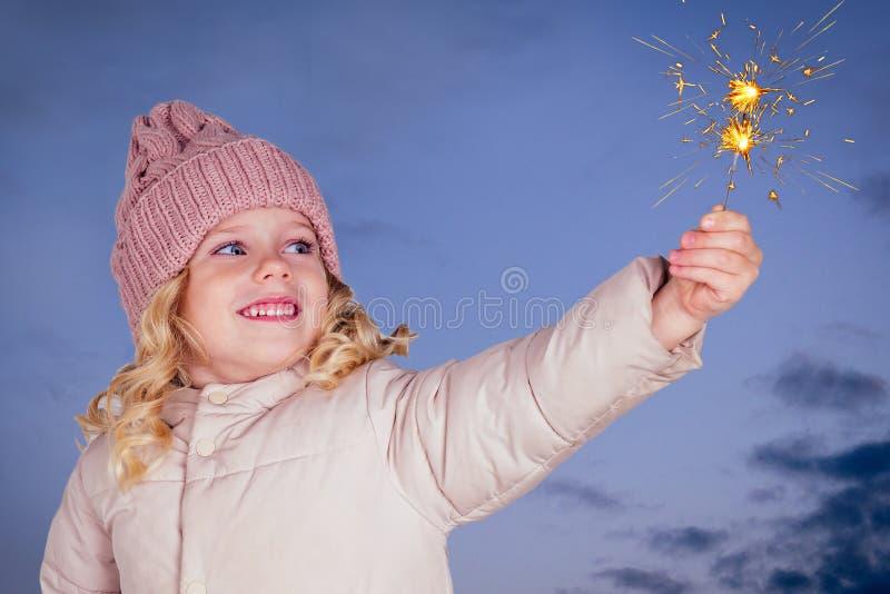 深蓝色背景中戴着烟花的针织帽的迷人小女孩 有xmas梦的金发美女 快乐 库存照片