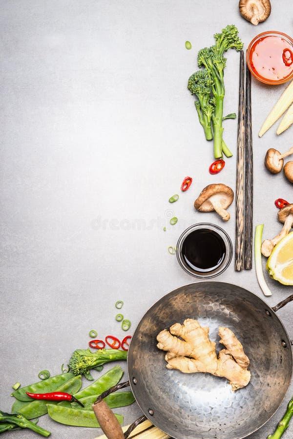 混乱与铁锅和筷子的油炸物成份 烹调在灰色石背景的亚洲烹调成份 免版税库存照片