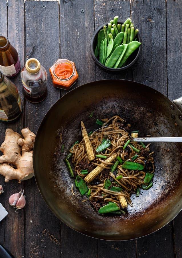 混乱油煎的牛肉和面条用牡蛎调味汁在铁锅,准备过程 免版税图库摄影