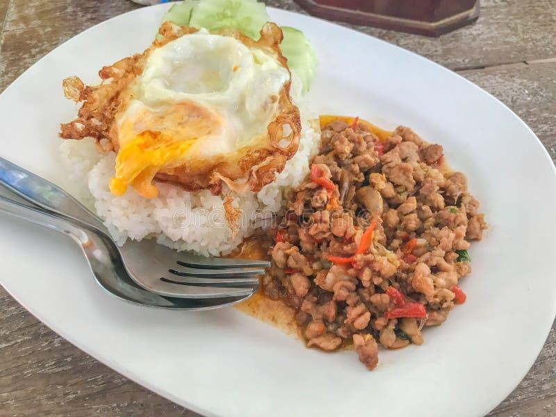 混乱油煎的猪肉和蓬蒿服务用米和荷包蛋 免版税库存照片