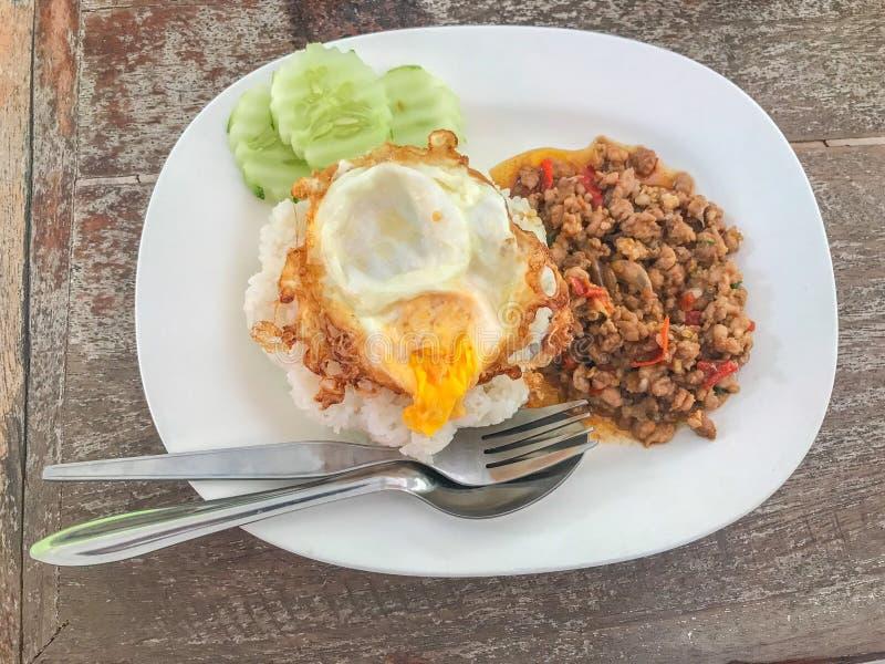 混乱油煎的猪肉和蓬蒿服务用米和荷包蛋 免版税库存图片