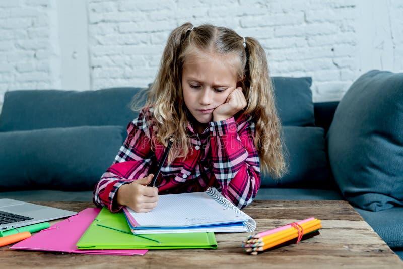 混乱逗人喜爱的小学生的感觉哀伤和,当在家做与她的膝上型计算机的困难的任务在小学时 库存照片