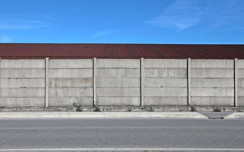 混凝土墙,有一条路的罐子棕色屋顶在前面 拷贝空间的都市背景 库存照片