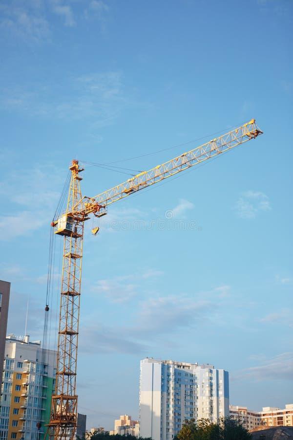 混凝土建筑和黄色塔吊反对蓝天背景 免版税图库摄影