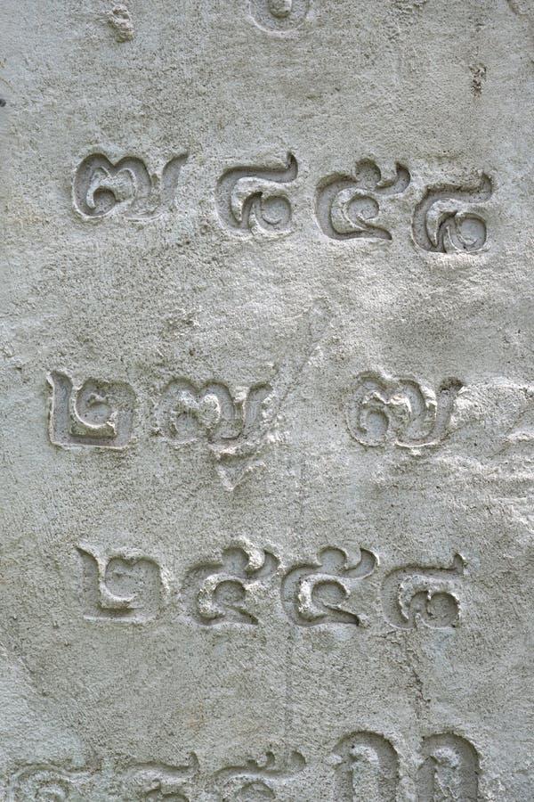 混凝土表面上刻有泰文数字字符、泰文字母 图库摄影