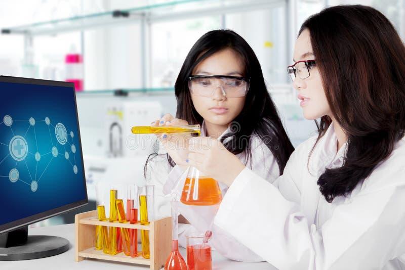 混合化学制品的年轻亚裔女性科学家 库存照片