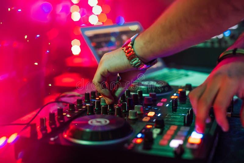混合和演奏在一台专业控制器搅拌器的手DJ音乐 免版税库存照片