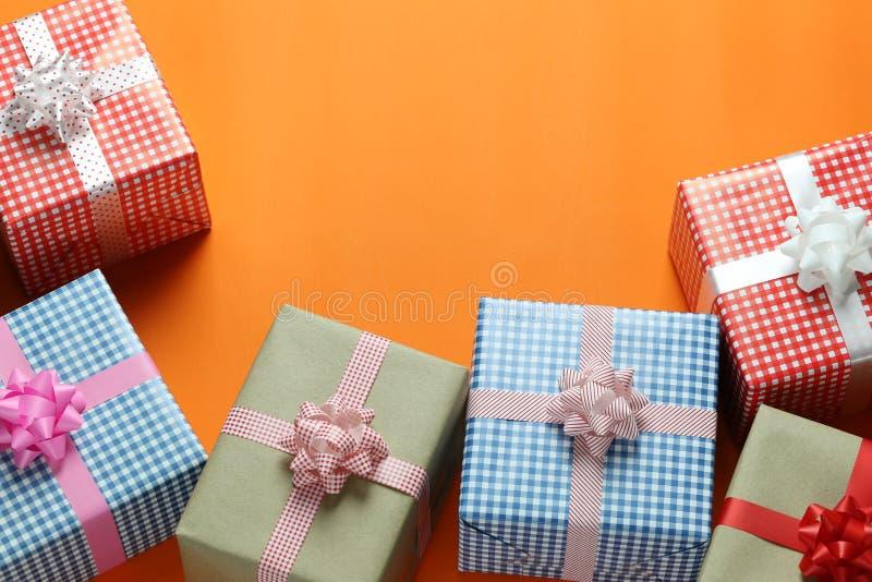 混合在一橙色加工印刷纸地板和ha安置的圣诞礼物箱子 库存图片