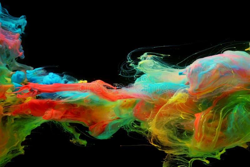 混合在水中的明亮的五颜六色的墨水云彩  免版税库存图片
