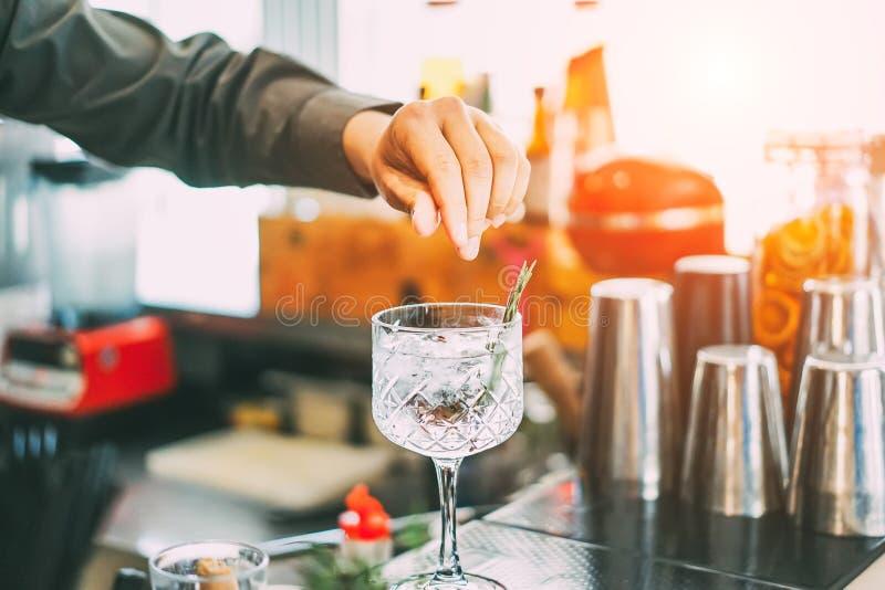 混合在水晶玻璃的侍酒者一个鸡尾酒与在美国酒吧的芳香草本在日落室外-男服务员在工作 库存图片