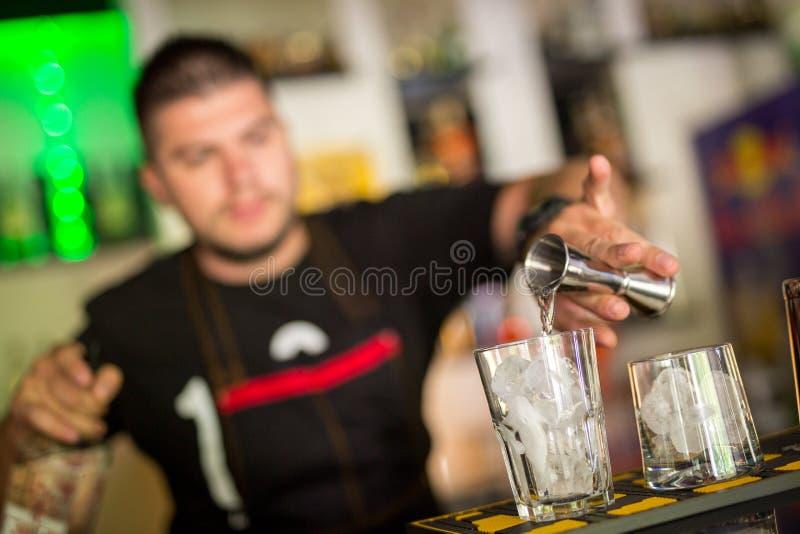 混合在酒吧的英俊的年轻男服务员一个鸡尾酒 免版税库存图片