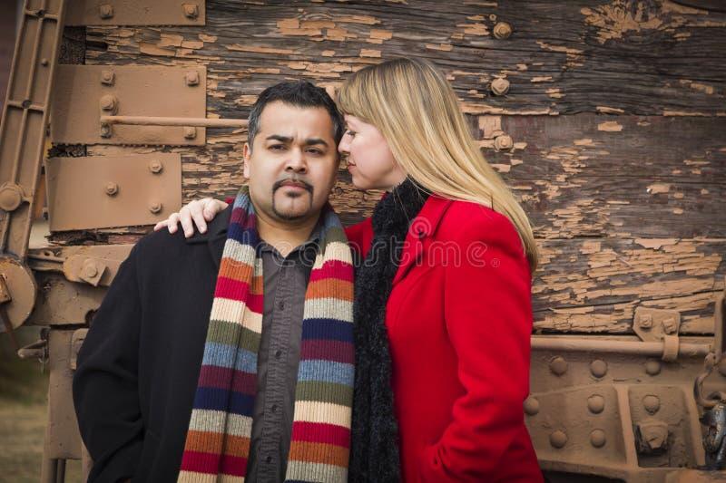 混合的族种在冬天衣物的夫妇画象反对土气火车 免版税库存照片