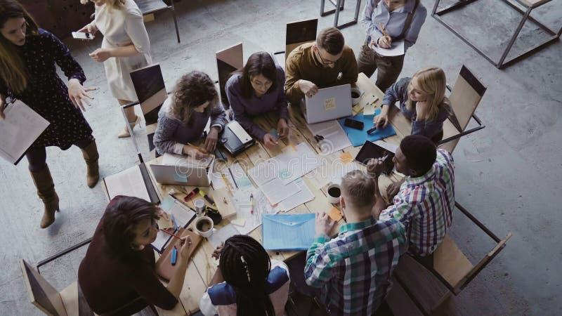 混合的族种坐在桌上的企业队顶视图在顶楼办公室和工作 妇女经理带来本文 免版税库存图片