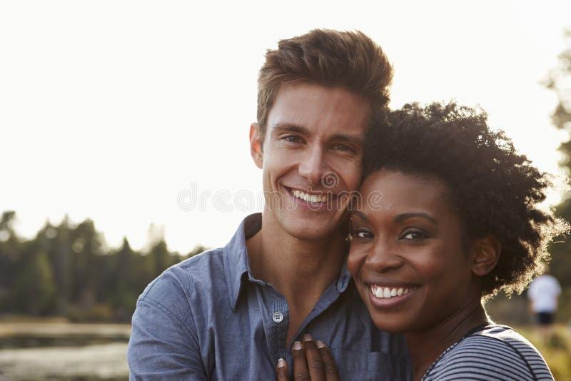混合的族种夫妇在乡下,看对照相机 免版税库存图片