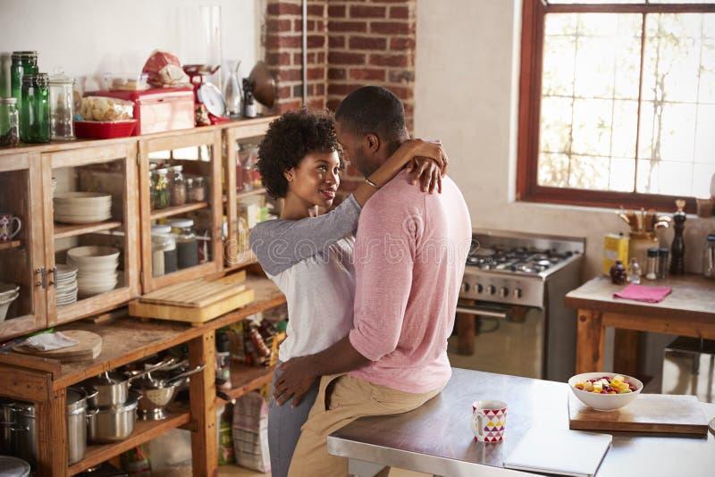 混合的族种夫妇在厨房里坐拥抱,大角度 库存图片