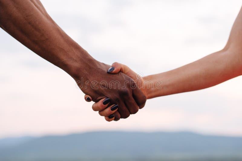 混合的族种夫妇特写镜头握在迷雾山脉背景的手 符号照片 免版税库存图片