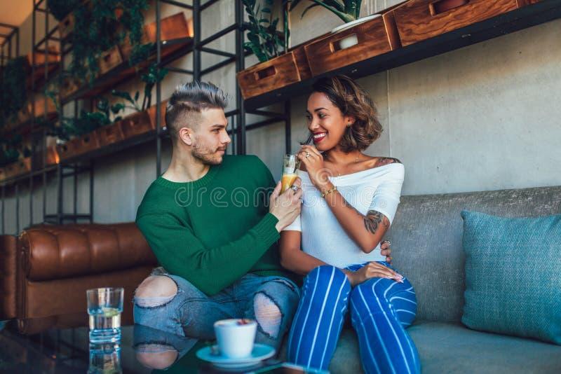 混合的族种夫妇获得乐趣在咖啡店 结合享用在咖啡店,坐在桌和笑上 免版税库存照片