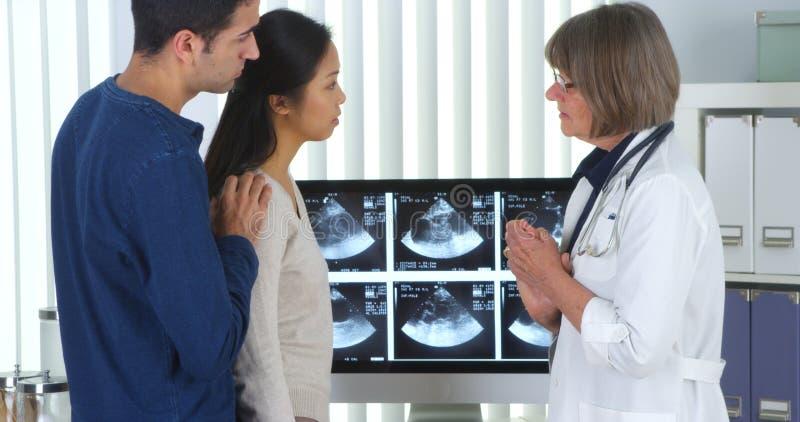 混合的族种夫妇谈话与关于他们新的婴孩的医生 图库摄影