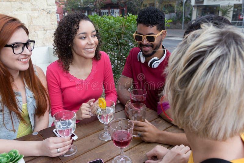 混合的族种小组朋友获得乐趣在餐馆外面 Sp 库存图片