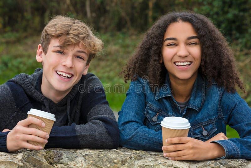 混合的族种少年男孩&非裔美国人女孩饮用的咖啡 图库摄影