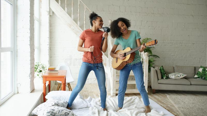 混合的族种年轻滑稽的女孩跳舞唱歌与hairdryer和弹在床上的声学吉他 有的乐趣姐妹 图库摄影