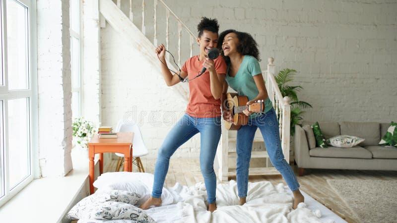 混合的族种年轻滑稽的女孩跳舞唱歌与hairdryer和弹在床上的声学吉他 有的乐趣姐妹 库存照片