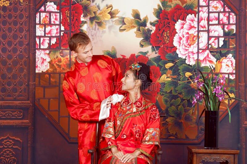 混合的族种新娘和新郎在穿繁体中文婚礼服装的演播室 免版税图库摄影