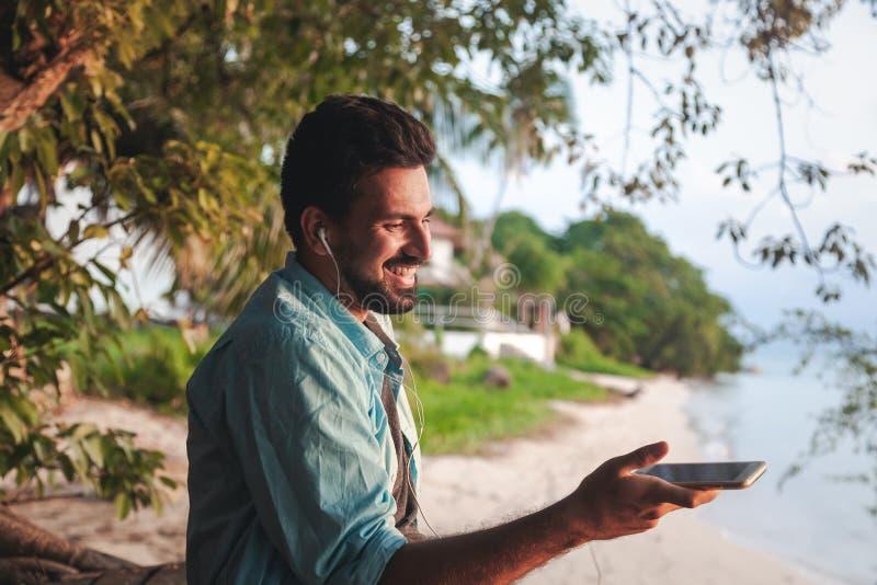 混合的族种有胡子的人拉丁美洲人的年轻可爱的人听到在耳机的音乐的,户外 免版税图库摄影
