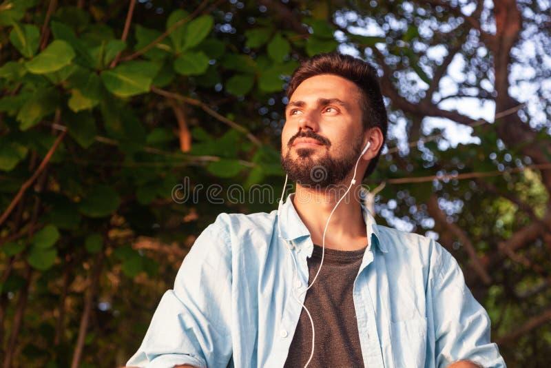 混合的族种有胡子的人拉丁美洲人的年轻可爱的人听到在耳机的音乐的,户外 图库摄影