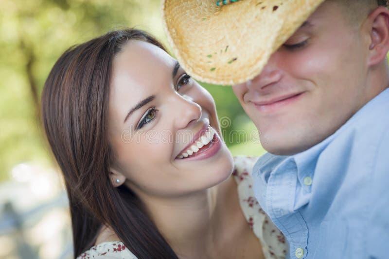 混合的族种浪漫加上挥动在公园的牛仔帽 库存照片