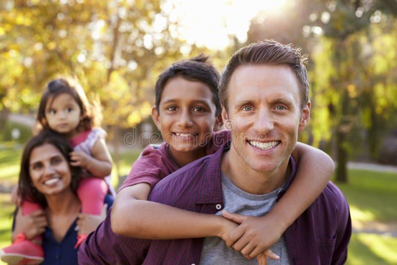 混合的族种父母运载孩子扛在肩上,选择聚焦 免版税图库摄影