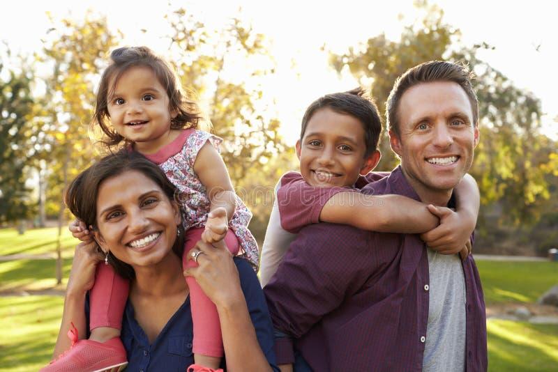 混合的族种父母运载他们的孩子在公园扛在肩上 免版税库存照片