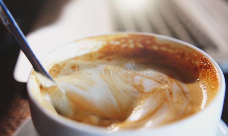 混合的有机糖到一个杯子拿铁咖啡里,慢动作 免版税库存图片