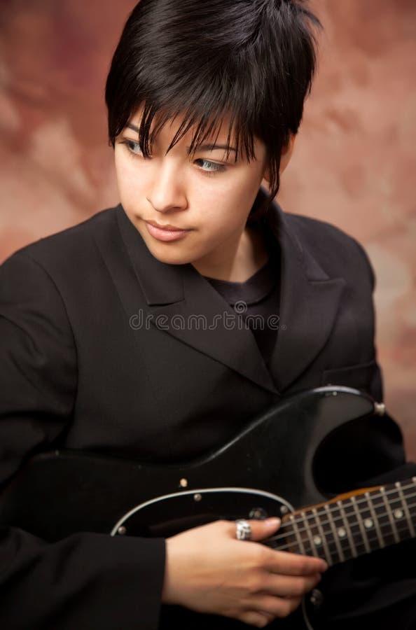 混合的电女孩吉他摆在青少年的种族 免版税库存图片