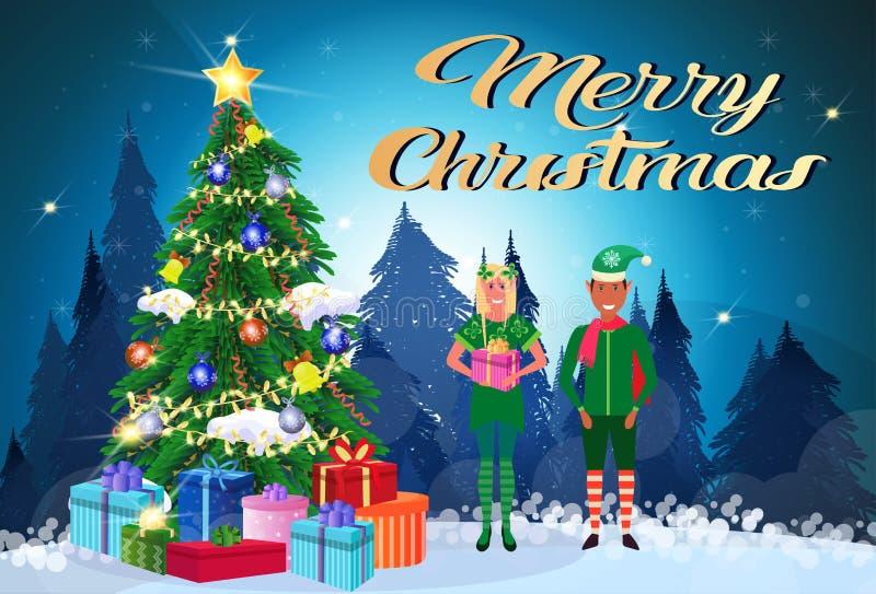 混合种族夫妇矮子服装藏品在杉树新年快乐平展圣诞快乐概念附近的礼物盒身分 皇族释放例证