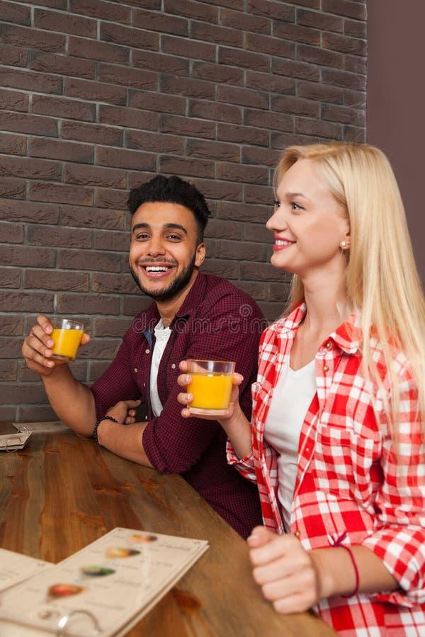 混合种族男人和妇女举行玻璃用橙汁坐在酒吧咖啡馆的木表上 库存照片