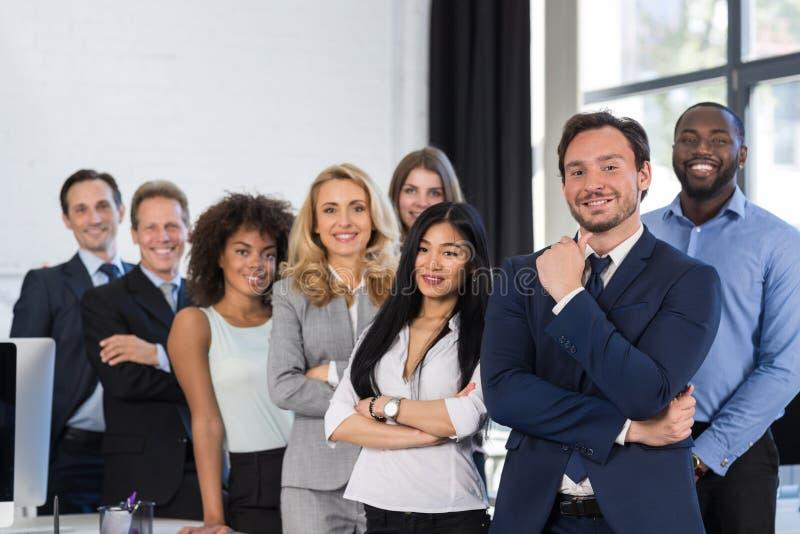 混合种族站立在现代办公室、买卖人愉快的微笑的商人和女实业家的商人小组 免版税库存图片