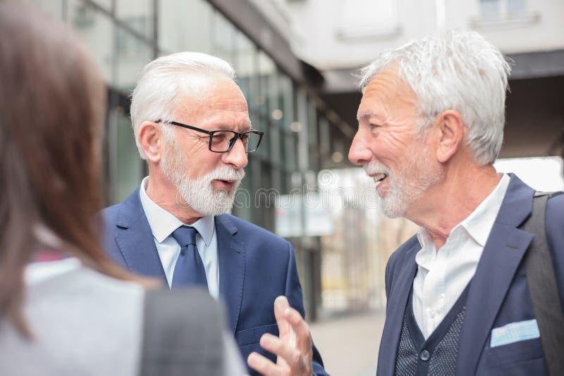 混合群买卖人见面和谈论在办公楼前面 免版税库存照片