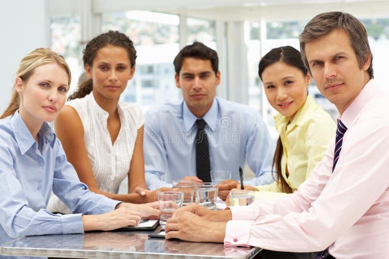 混合群在业务会议在表附近坐了 免版税库存照片