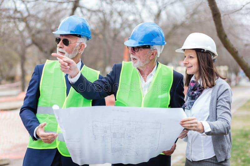 混合群建筑师和商务伙伴谈论项目细节在工地工作的检查时 免版税库存照片