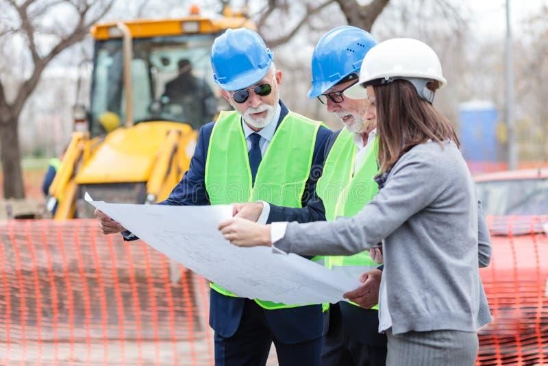 混合群的建筑师和谈论的商务伙伴在工地工作的项目细节 免版税库存照片