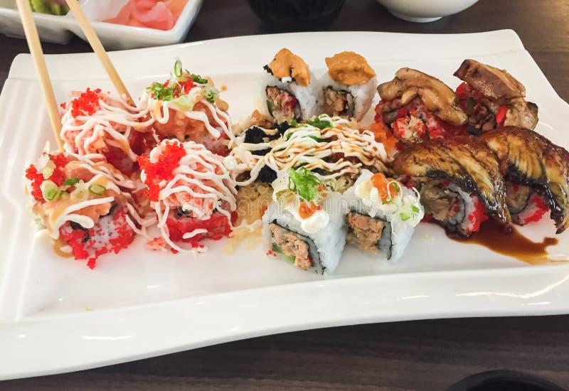 混杂的寿司,日本食物,安排在白色板材 免版税库存图片