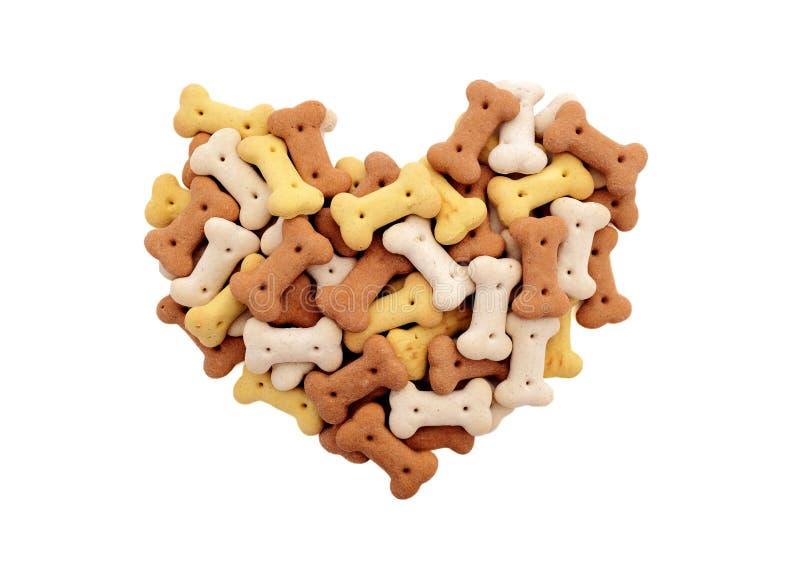 混杂的干喂狗的硬饼干在心脏塑造 免版税库存图片