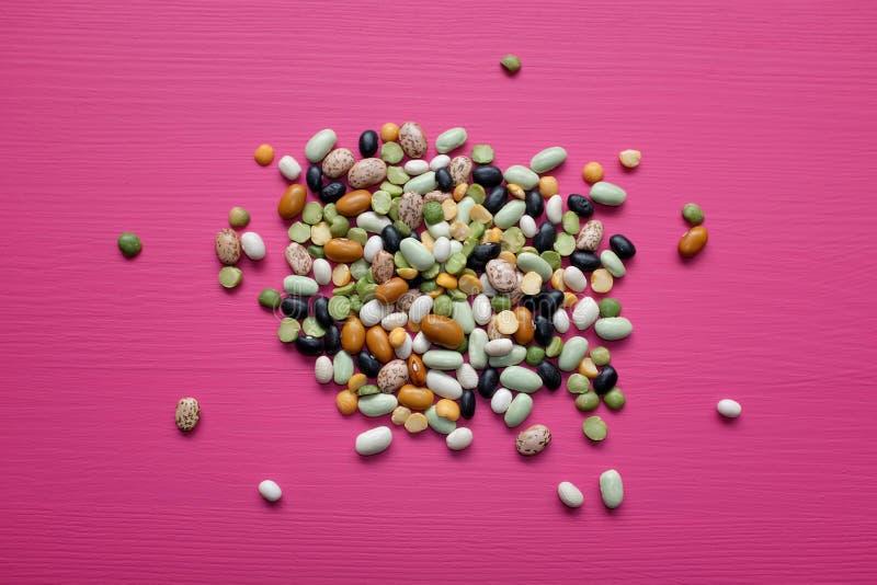 混杂的干豆和豌豆在桃红色背景 库存图片