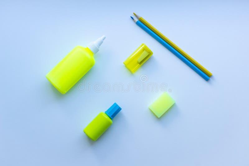 混杂的文具顶视图在黄色和蓝色颜色的:胶浆、磨削器、橡皮擦、两支铅笔和修正液在白色backgr 库存照片
